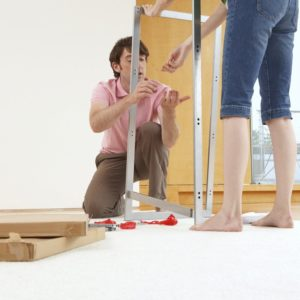 homme et femme assemblant meuble